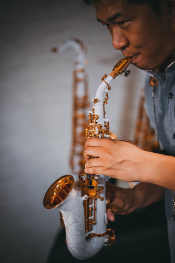 Man Playing Saxophone Against Wall