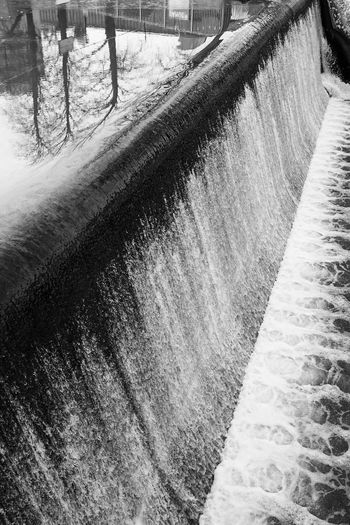 High angle view of dam by canal during winter