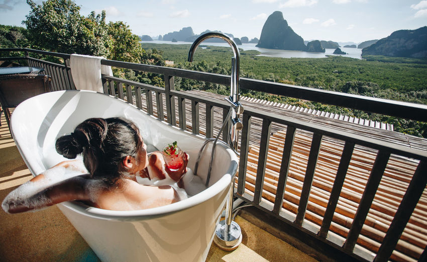Real People Lifestyles Water Bathtub One Person Food And Drink Leisure Activity Domestic Bathroom Nature Railing Taking A Bath Day Headshot Drink Young Adult Refreshment Balcony Bathroom Outdoors