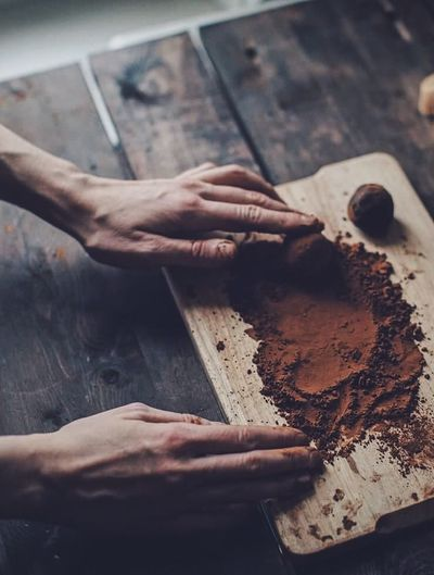 Cropped hands of person by cocoa powder on cutting board