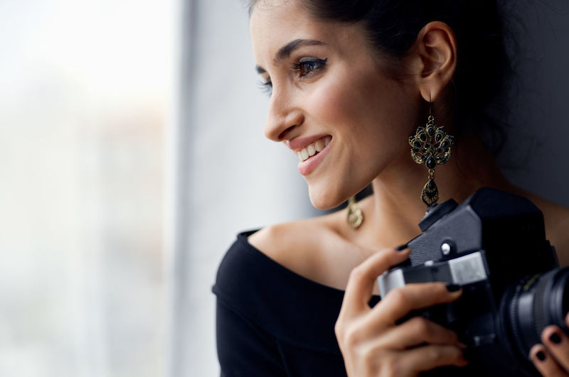 Portrait of a smiling young woman holding camera