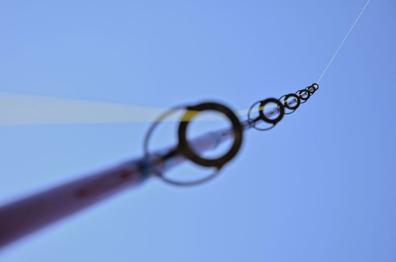 Low angle view of eyeglasses against blue sky