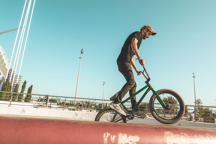 Side view of young man riding bicycle against clear sky
