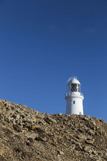 Portland Bill Lighthouse against blue sky, Portland Dorset, UK Architecture Blue Building Building Exterior Built Structure Clear Sky Copy Space Day Direction Guidance Lighthouse Low Angle View Nature No People Outdoors Protection Safety Security Sky Sunlight Tower