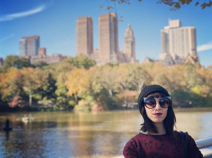 Portrait of woman wearing sunglasses against lake in city