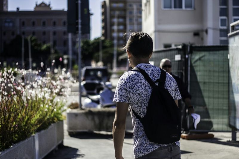 Rear view of man with backpack walking by buildings in city