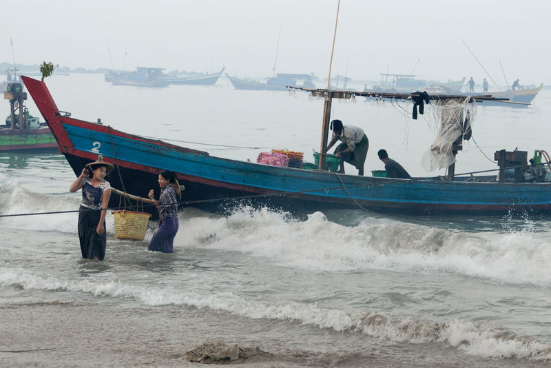 The surf is rolling in while these two women get wet unloading the fishing boat. Fishing Village Rakhine State Surf Architecture Beach Day Fishing Boat Horizon Over Water Men Mode Of Transport Myanmar Nature Nautical Vessel Outdoors People Real People Sea Sky Transportation Water Wave
