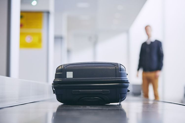 Young man waiting for luggage while standing by conveyor belt at airport