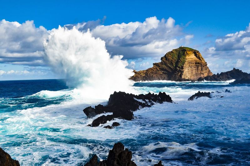 Panoramic view of sea and rocks against blue sky