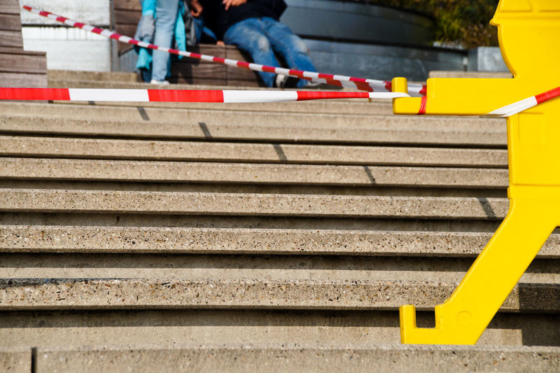 Cordon tape over steps against friends on seat