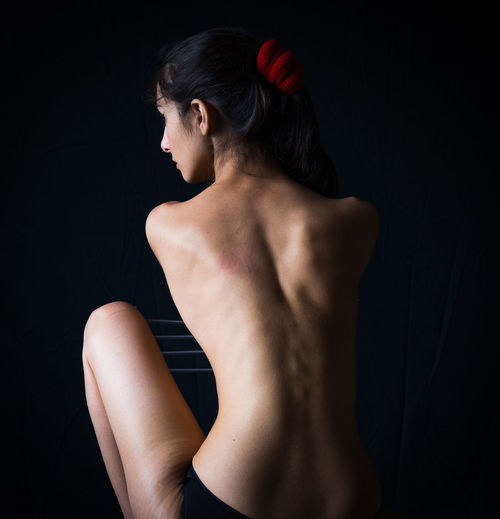 Rear view of shirtless young woman against black background