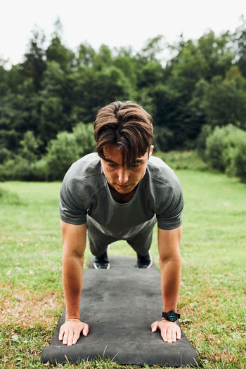 Young man doing push-ups outside on grass during his calisthenics workout
