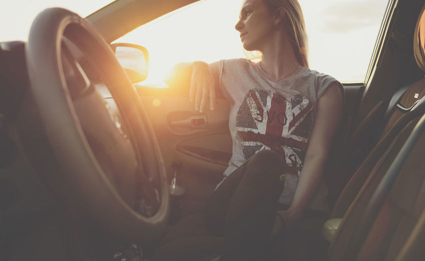 Thoughtful woman sitting in car during sunset