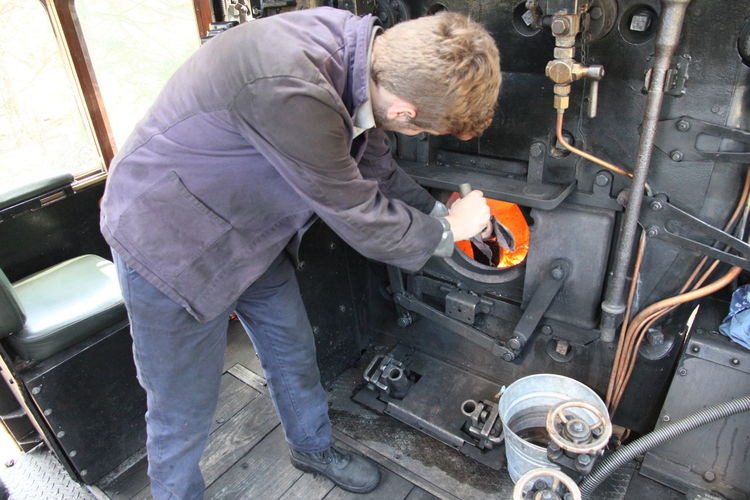 High angle view of train engineer working in steam train