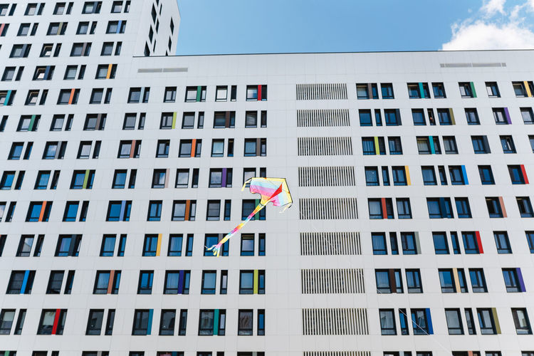 Low angle view of kite flying against buildings in city