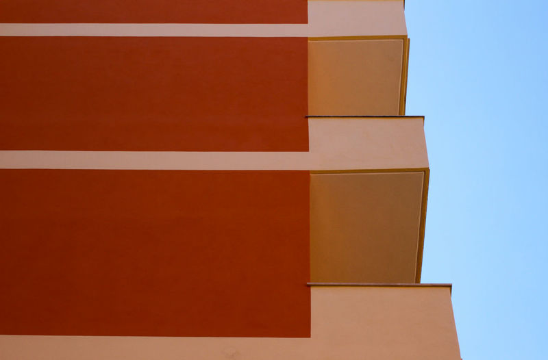 Low angle view of orange building against clear sky