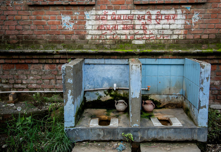 View of dirty unhygienic toilets next to brick wall
