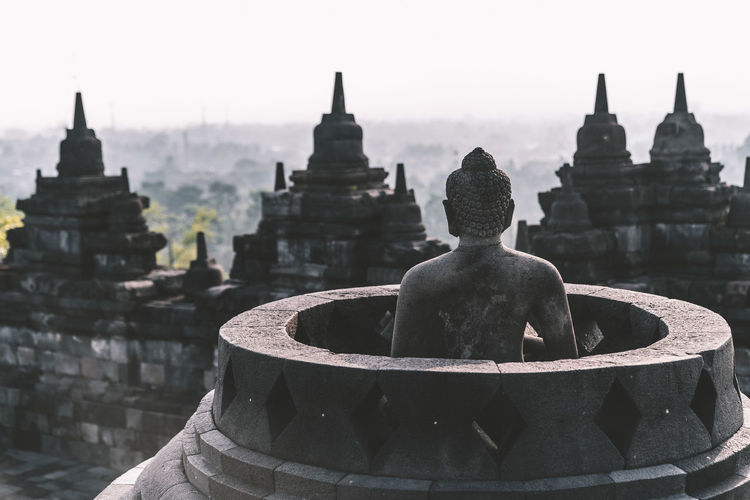 Buddha statue in temple against sky