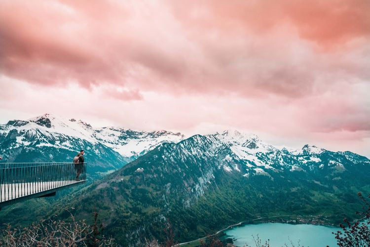 Man looking at snowcapped mountains against cloudy sky