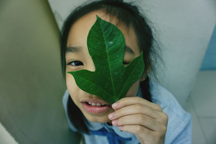 Close-up high angle portrait of girl covering eye with leaf