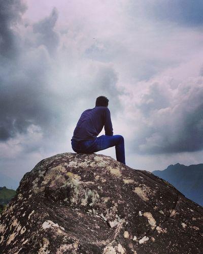 Man sitting on rock against mountain