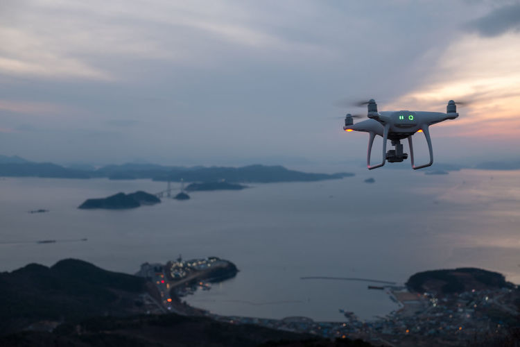 Flying drone Aerial View Air Vehicle Beach Beauty In Nature Camera - Photographic Equipment Cityscape Day Drone  Flying Helicopter Media Equipment Mid-air Mountain Nature No People Outdoors Photography Themes Scenics Sea Sky Sunset Technology Water