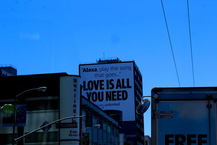 Low angle view of signboard against blue sky