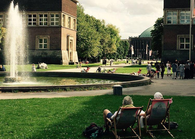People in park against buildings in city