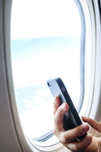 Closeup of hands holding and using mobile phone on board an airplane near window Copy Space Natural Light Airplane Close-up Communication Connection Day Flying Hand Holding Inflight Mobile Device Mobile Phone Sky Smart Phone Technology Travel Using Window Wireless Technology