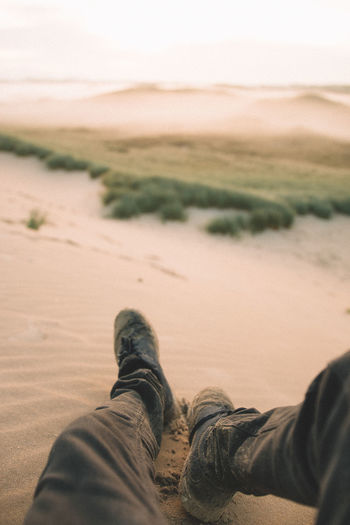 Low Section Of Man Relaxing On Sand At Beach