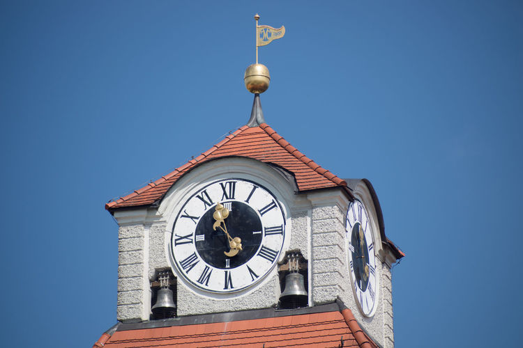 Low angle view of clock tower against clear blue sky