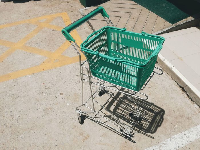 Green trolley is outdoors. Shopping Cart Supermarket Retail  Consumerism High Angle View Communication Trolley Western Script Written Board No Parking Sign Text Road Sign Warning Sign Warning Information Sign Information Parking Sign Directional Sign Signboard Arrow Sign Arrow Symbol Price Tag Capital Letter