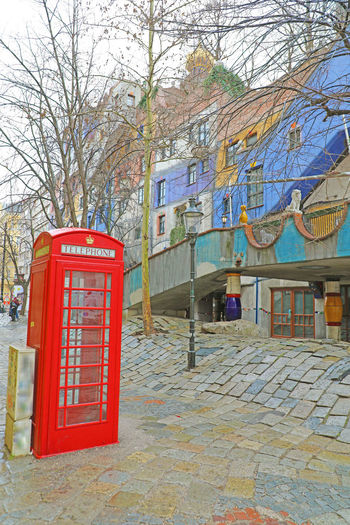 Red phone booth in Vienna street with Hundertwasserhaus Architecture Built Structure Building Exterior Building City No People Day Outdoors Red Telephone Tree Telephone Booth Communication Pay Phone Nature Bare Tree Branch Plant Connection Red Phone Booth In Vienna Red Phone Booth Red Phone Box Red Phone Vienna Hundertwasserhaus