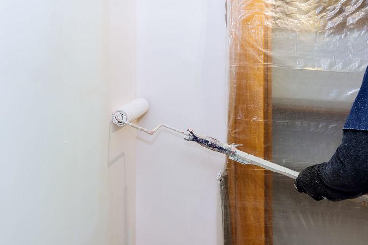 Man painting wall at home