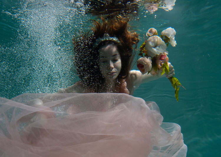 Woman holding flowers while swimming in pool