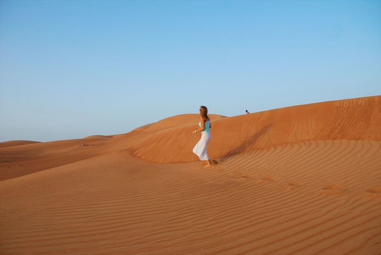 Woman walking on sand dune in desert against clear sky