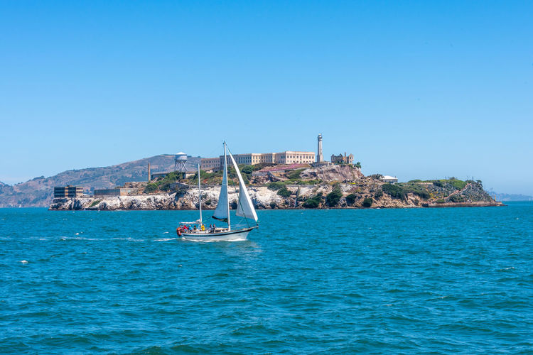 Alcatraz Prison Sea Water Nautical Vessel Transportation Sky Mode Of Transportation Waterfront Blue Clear Sky Day Beauty In Nature Nature Scenics - Nature Copy Space Sailing Travel Sailboat Land Outdoors Turquoise Colored