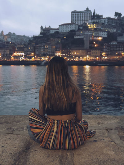 Rear view of woman sitting at promenade in city during dusk