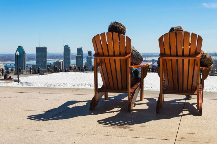 Montreal, CA - 30 March 2017: People sitting on a wooden lawn chair and enjoying a sunny spring day on Kondiaronk Belvedere Cityscape Mont Royal Montreal, Canada Mount Royal Skyline Snow ❄ Winter Beauty In Nature Canada Long Chair Outdoors Real People Rear View Snow Spring Sunlight
