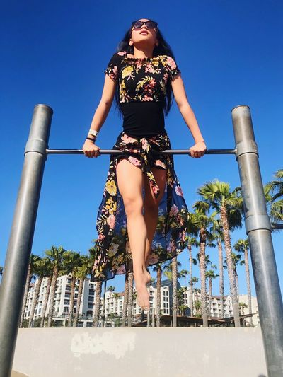 Low angle view of teenage girl holding railing against clear blue sky