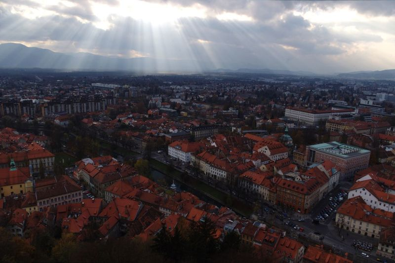 Townscape against sunbeams streaming from sky