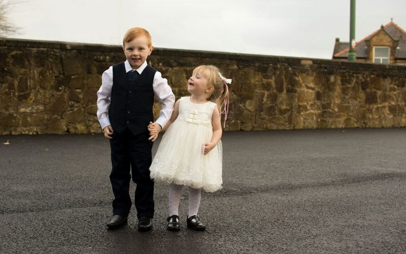 Happy Well-Dressed Siblings Holding Hands While Standing On Road