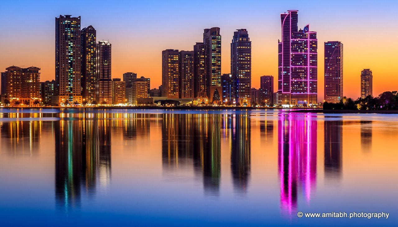reflection, architecture, skyscraper, building exterior, illuminated, night, cityscape, city, built structure, modern, waterfront, urban skyline, water, outdoors, travel destinations, sky, sunset, no people