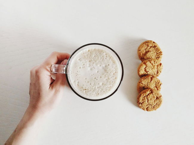 About to enjoy breakfast. Breakfast Latte Cappuccino Cookie Directly Above Drink Drinking Glass Food Food And Drink Freshness Frothy Drink Holding Human Body Part Human Hand Indoors  One Person Ready-to-eat Real People Refreshment Table White Background