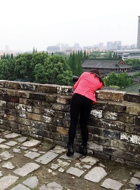 Girl Taking Photos Athleisure Red Cloth Black Pants Athleisure Pants Ancient Walls Buildings Trees Camera Outdoors Hidden Gems  Colour Of Life Eyeemphoto A Bird's Eye View People And Places