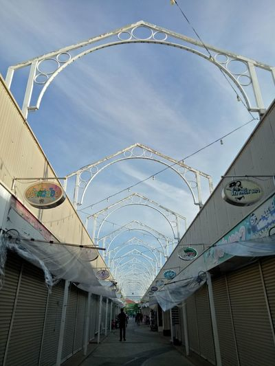 Low angle view of people walking on bridge against sky