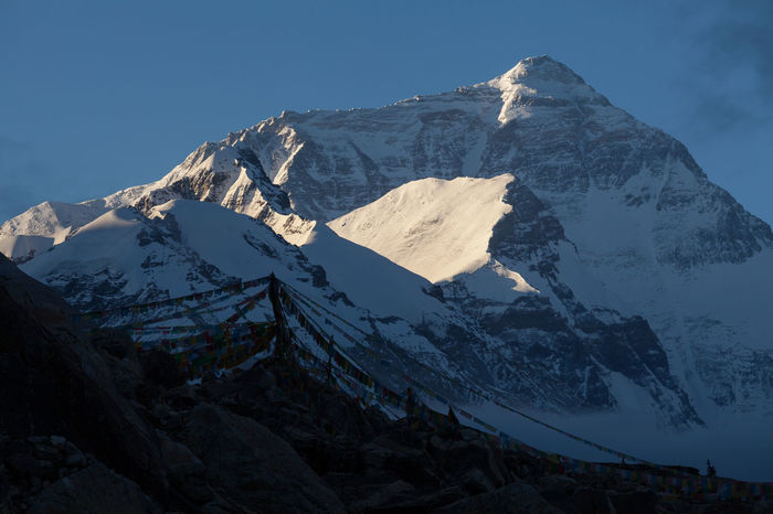 Morning view of Mount Everest from Tibet Everest base camp, Tibet, China, with the silhouette of colored prayer flags. Belief Blue Blue Sky Buddhism Devotion Flag Himalayan Himalayan Range Himalayas Landscape Morning Mountain Mountain Range Prayer Flags  Religion Silhouette Wanderlust