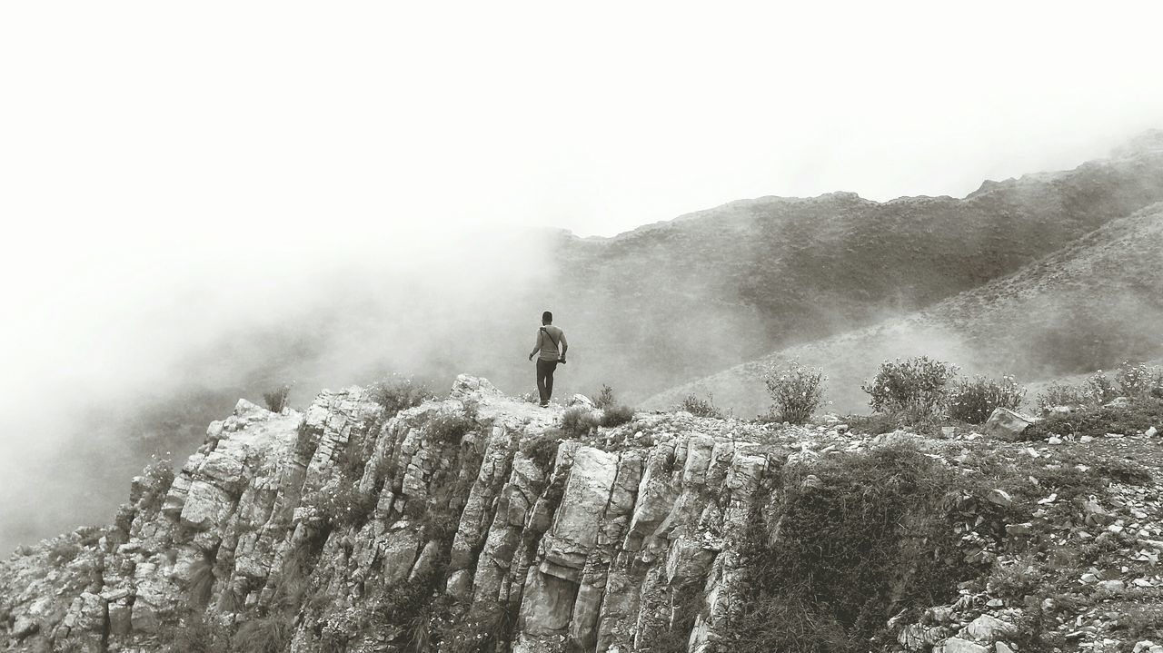 Rear View Of Man Walking On Rock Formation Against Sky