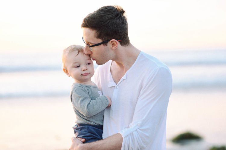 Young man with daughter standing at beach