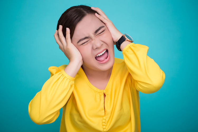 Angry woman on isolated background Yellow Blue Background Angry Woman Isolated Portrait Upset Frustrated Stress Bad Frustration Expression Hair Screaming Shouting Rage Attractive Lifestyles Scream Looking ShoutOut Emotion Emotional Sad Sadness